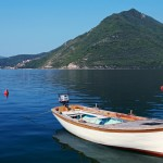 White wooden fishing boat floats moored in Perast town, Adriatic